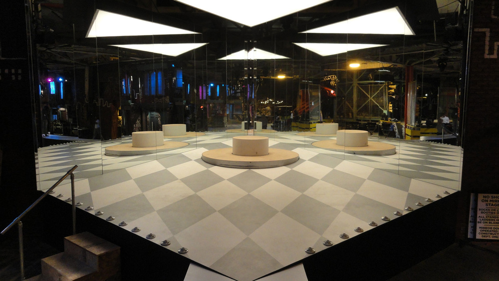 In the story, club Off the Streets is a well known venue for top hip hop acts. This is a stage/set piece built specifically for a performance by the popular young star Roxxie (Coco Jones). It is ultimately a huge triangular, mirrored room for several beats of the song, which creates an infinite efffect, reflecting Roxxie's image and the harlequin-checkered floor thousands of times. Here only two of the walls are in. The third wall was installed by a crane overnight, and consisted of two 12'x16' sliding doors that weighed 1,200 pounds each.