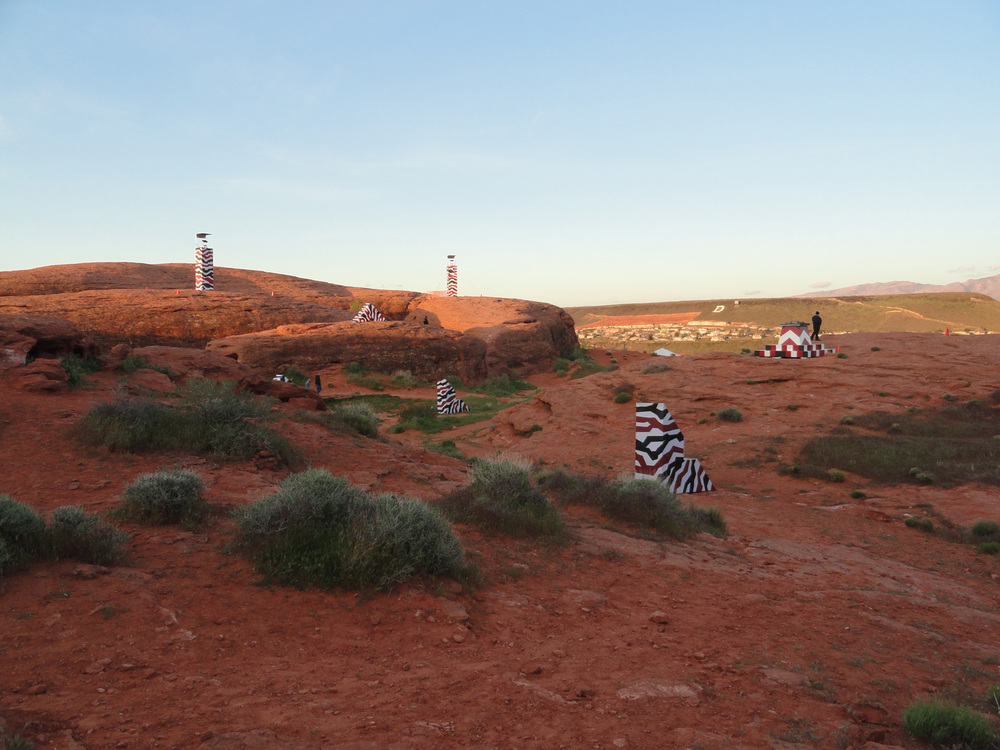 A view of the desert paintball battlefield complete with spotlight towers and battle barriers.