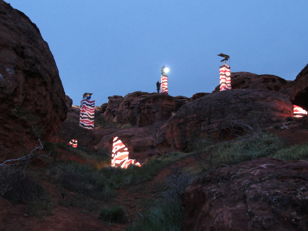 A night-view of the desert paintball battlefield with internally-lit spotlight towers and battle barriers.