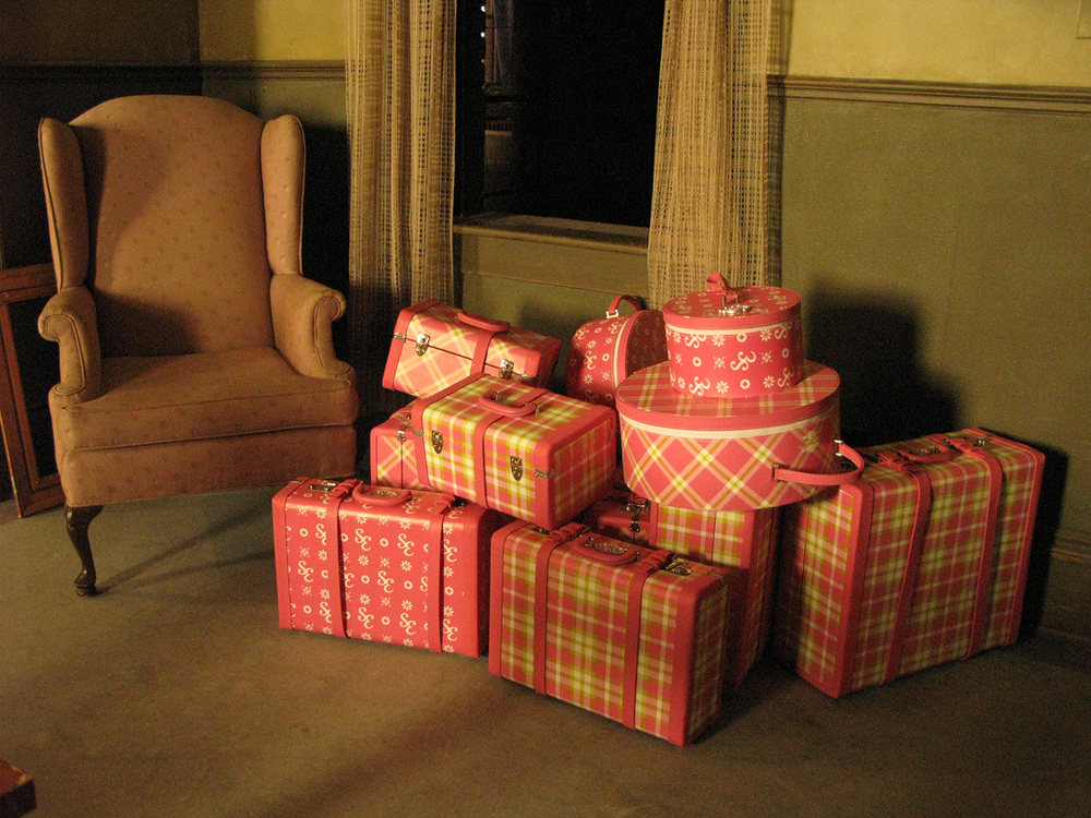 A detail of the luggage we created for Sharpay (Ashley Tisdale) with custom designed plaids and other patterns looking quite out of place in this dismal, post-war green apartment stage set.
