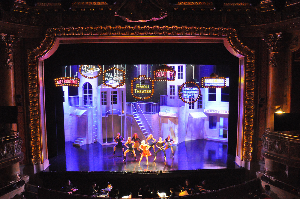 "Another moment in the opening number of ""A Girl's Best Friend"", with Broadway fantasy marquees descending above the stage. This was installed in Toronto's beautiful Elgin theater. Our schedule overlapped with theG20 summit, and the theater was well within the high security area. So we had to design the set to load-in in a few short hours before the lockdown, and rioting occurred outside the front doors as we were assembling it. It was an exciting day."