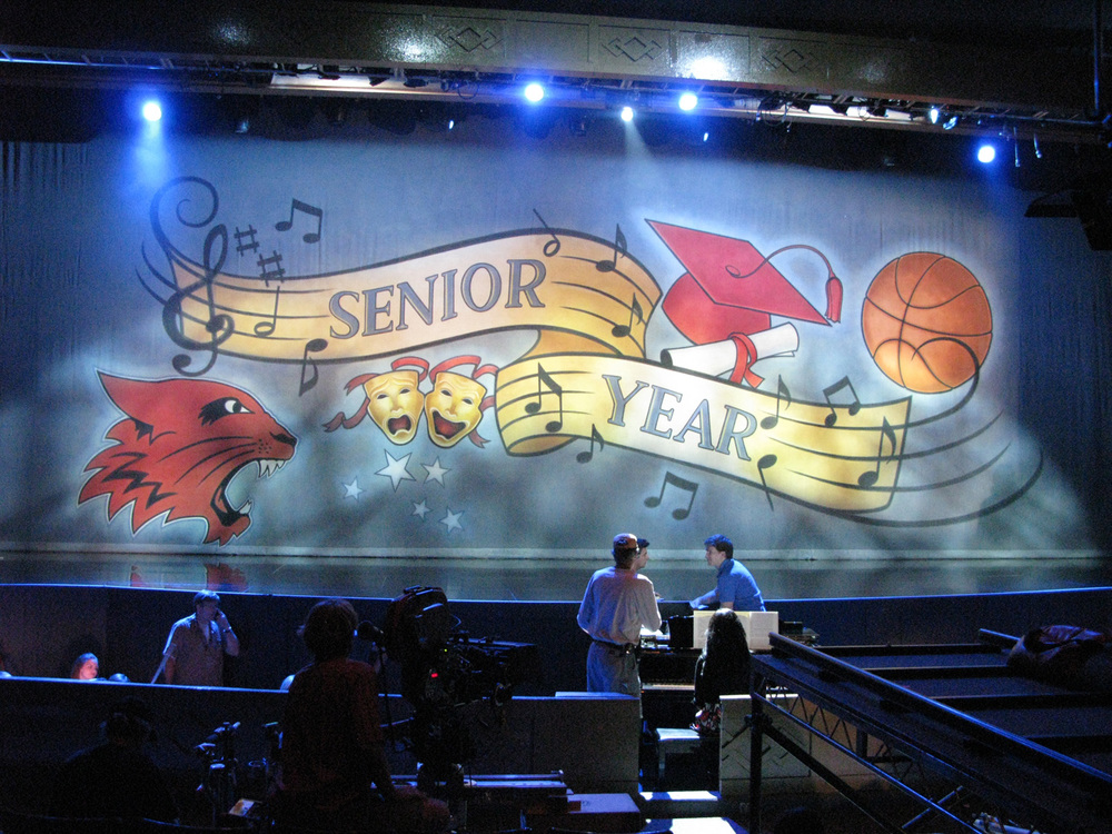 "Show scrim for the opening of ""Senior Year"". A lighting change from front to back-lit reveals basketball players in a stylized ""Gym"""