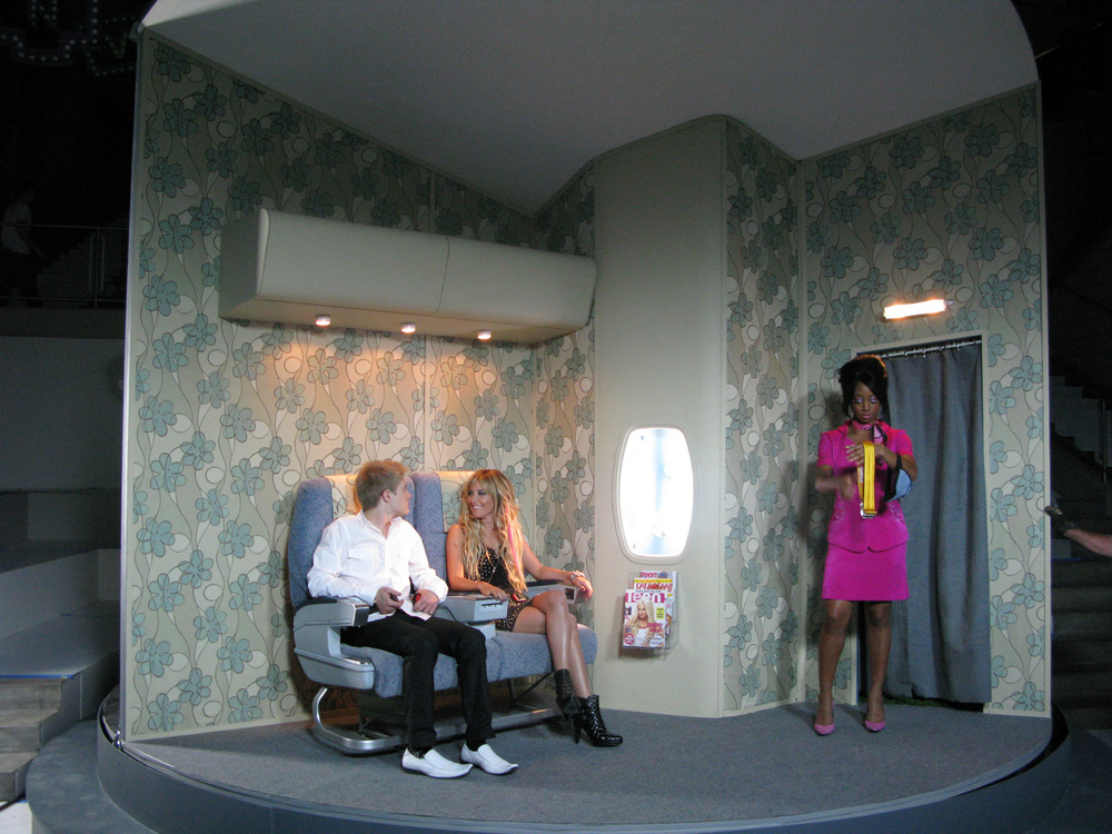 """First Class Cabin"", part of the opening sequence of ""I want it All"". We conceived of a moment in the song where overly-entitled twins Ryan (Lucas Grabeel) and Sharpay (Ashley Tisdale) imagine going on a fabulous trip. I created a very fun, vaudeville rotating set complete with fabulous 1960's Pan Am style stewardess (Monique Coleman) to accommodate this. Outside the window is a rotating column of sky with clouds and little birds."
