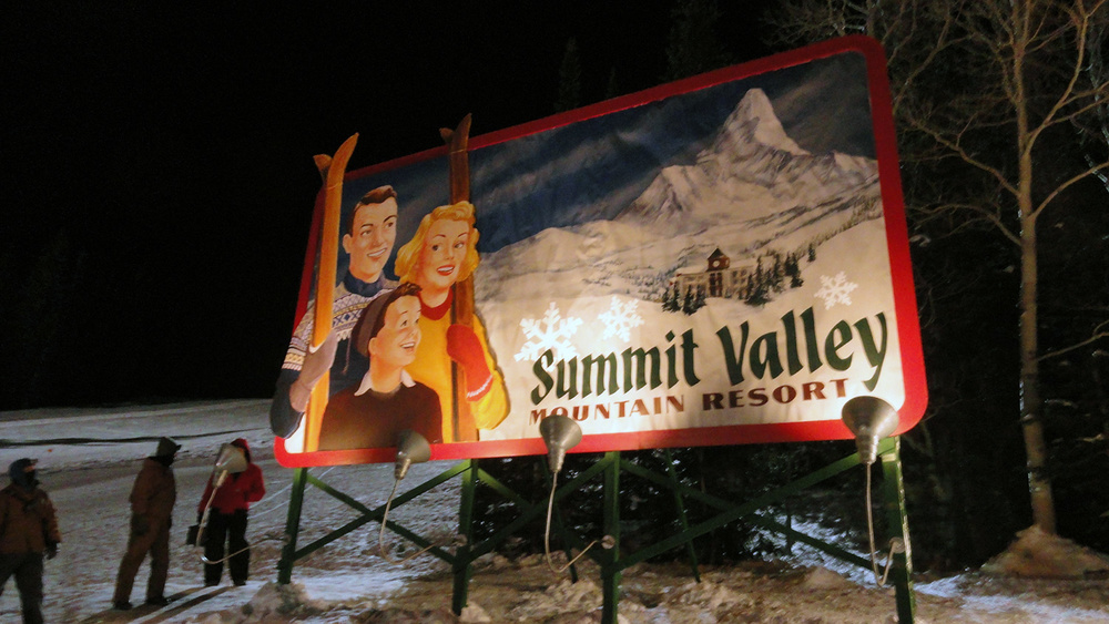 "The ""historic"" Summit Valley billboard. An escaped sled hurtles down the slope and crashes through the prized relic of the resort owner. Here it is rigged with det-cord, ready for a hole to be blown in it before it falls over and crashes on the snow."