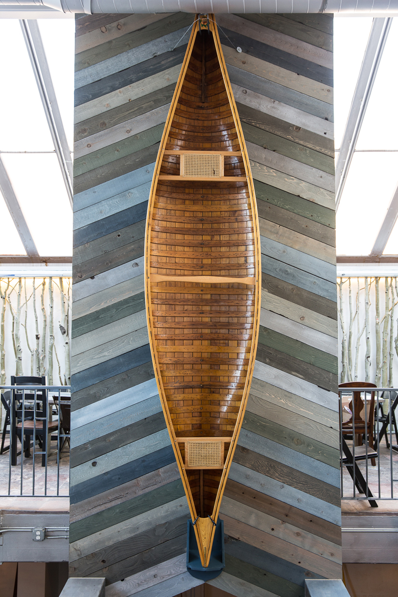 The WOW guys conceived of this central column to create some design continuity between the jumble of shape, form and period in the architecture. We custom stained this wood in the same frosty palette of the tables. The visual impact of the shallow diagonal combined with the beauty of the antique canoe accomplished the desired harmony perfectly.