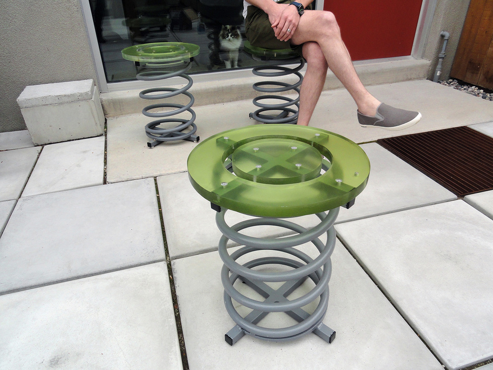 Spring chairs using 95% recycled materials. Springs are salvaged Second World War heavy truck springs, seats are salvaged 3-form plastic from a restaurant remodeling, square tube steel salvaged from struck movie-set.