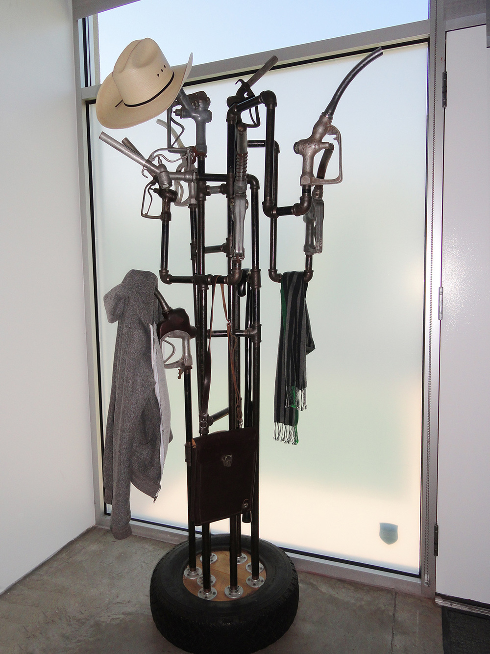 Coat rack, made from salvaged antique gas pump handles and black steel pipe and fittings. Mounted on a cement filled tire.