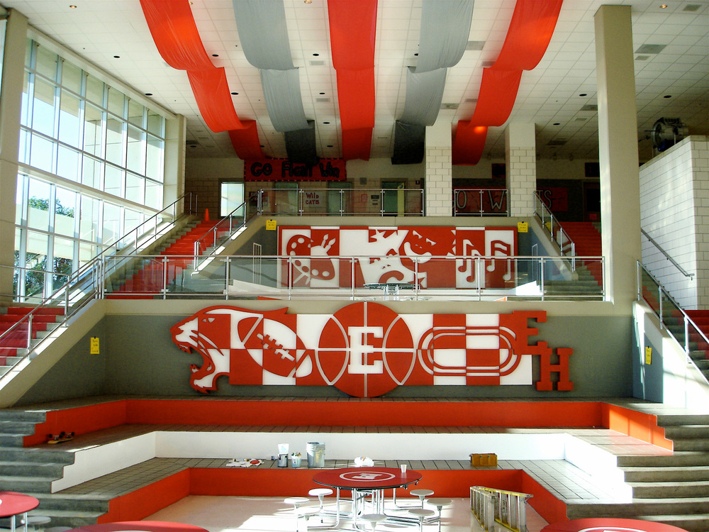 We loved the bones of this fantastic public school cafeteria, it was perfect for staging big, Busby Berkeley style dance numbers. But in it's original form it was far too bland for our idealized high school. Inspired by a recent trip to see the work of the great muralists of Mexico, I divided high school into three concepts and did a foam-cut mural for each; The Arts (top of frame), Athletics (center frame), and Academics (not pictured).
