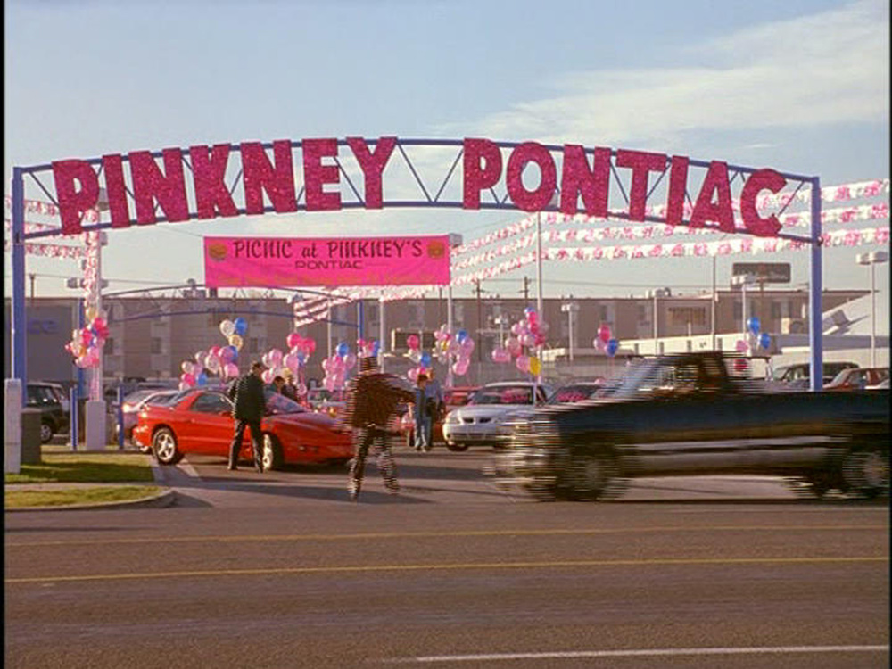 Signage and parking lot sale of slimy car salesman Norman Pinkney's (Ed O'Neill) Pontiac dealership.