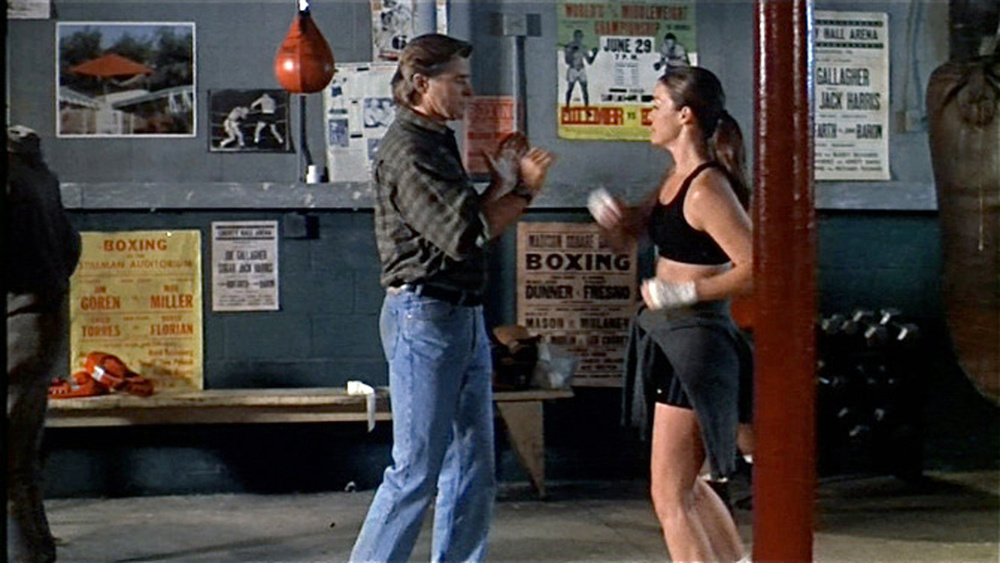 Mercenary Karl (Treat Williams) visits lady assasin Andy (Claudia Christian) in her gritty boxing gym, stage set.