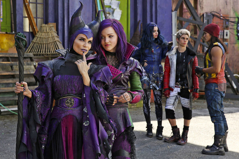 "Mal (Dove Cameron) conspires with her mother Maleficent (Kristin Chenoweth) on the Isle of the Lost. The Isle is a combination of Alcatraz, a Turkish Bazaar and John Water's Baltimore. With the entirety of Disney's stable of villains imprisoned here, the color palette had to reflect their very particular taste. After a careful study of classic Disney villainy, I took all their purples, blacks, burgundies, and acid greens, and drenched them with 20 years of soot, rust, grime and grit. I called the resulting palette ""Dirty Candy"".  (Disney Publicity photo)"