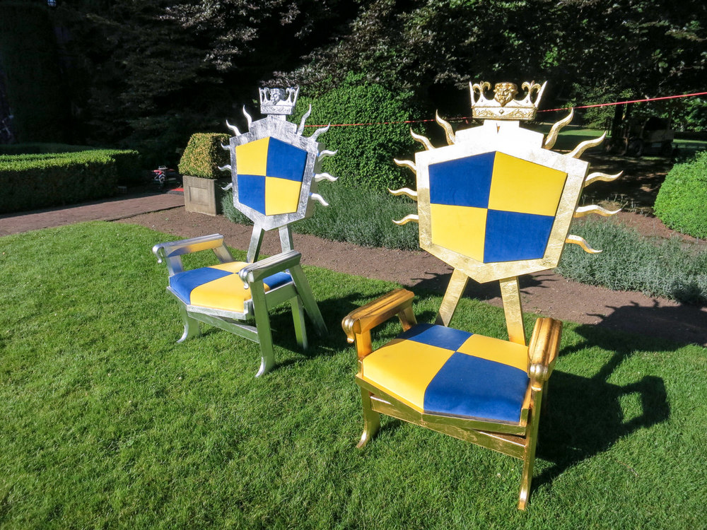 "A shot of the thrones of the King and Queen of Auradon. Note that the shape of the back rest is also that of all of Auradon's federal signage. The structure of the back and sides of the thrones are ""A's""."