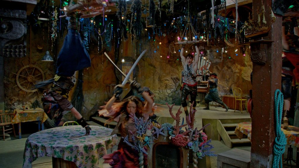 """Harry Hook (Thomas Doherty) Swings from a chandelier during """"What's My Name"""" In Ursula's Fish and Chips Shoppe."""