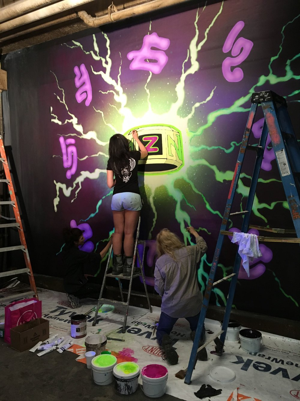 Artist Aurora Kruk works on a mural celebrating the Z-Band, the device that restored the zombie's humanity.