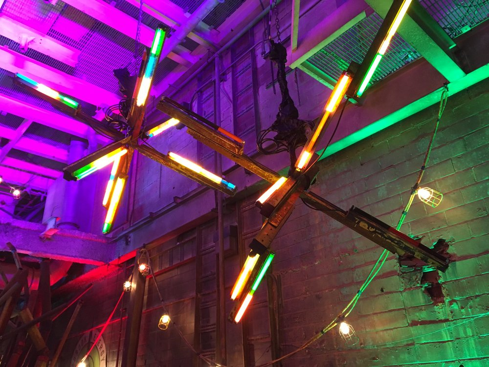 """Our jumping jack lights were made by wrapping 2' florescent tubes in overlapping layers of colored gel, then screwing loads of those fixtures to angle iron """"jacks""""."""