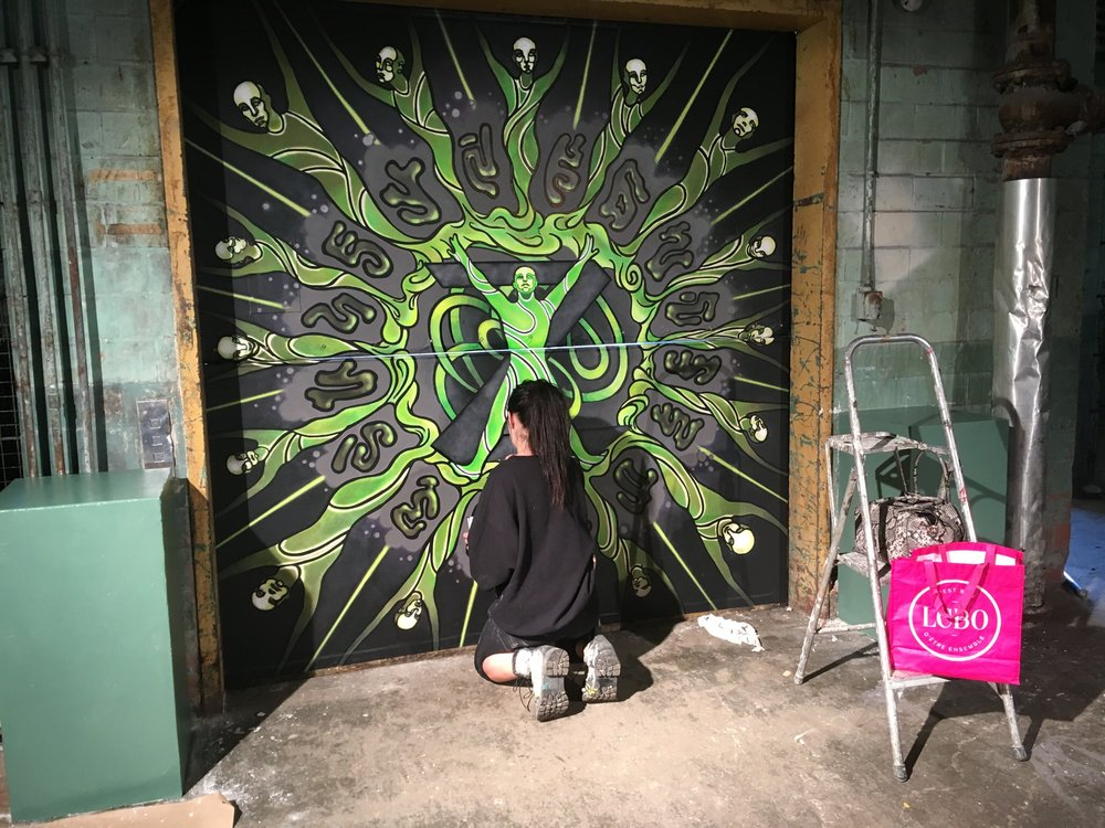 Here Aurora Kruk works on the mural celebrating the moment of genesis of the first Zombie, Z.