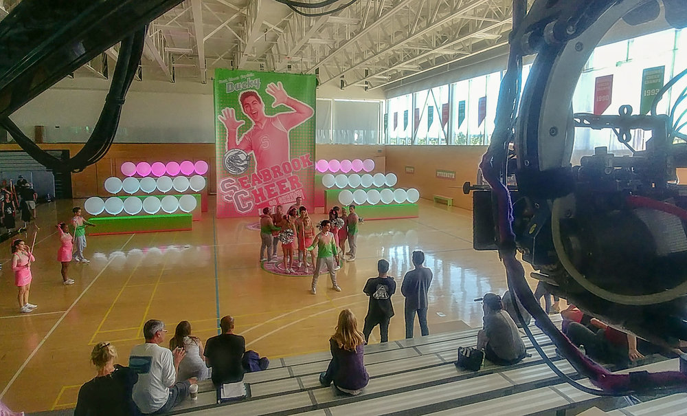 """The cult of cheer captain Bucky (Trevor Tordjman) is expressed in near religious terms at Seabrook high. The pep rally is an expression of that cult of personality. LED color bars illuminate the perfectly spaced, 36"""" balloons that frame his layered graphics."""