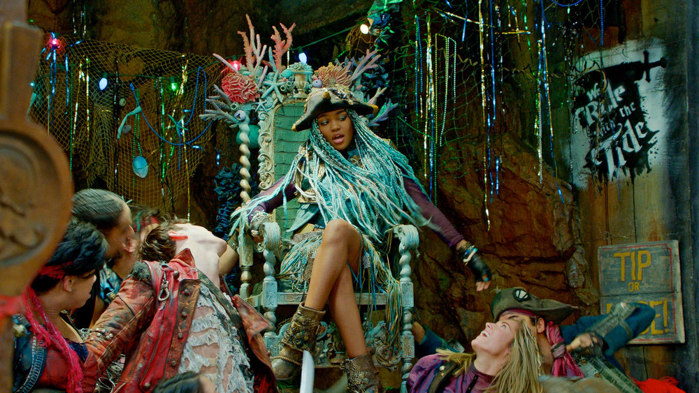 "Uma (China Anne McClain) commanding respect on her coral throne in Ursula's Fish and Chips Shoppe. Note the ""We Ride With the Tide"" iconic street art we developed for her pirate gang."