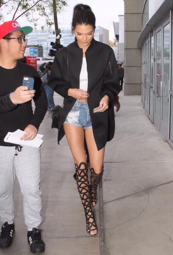 Kendall in an oversized black bomber, denim cut-offs, and Sophia Webster cut-out knee-highs / Via  Michael Maven