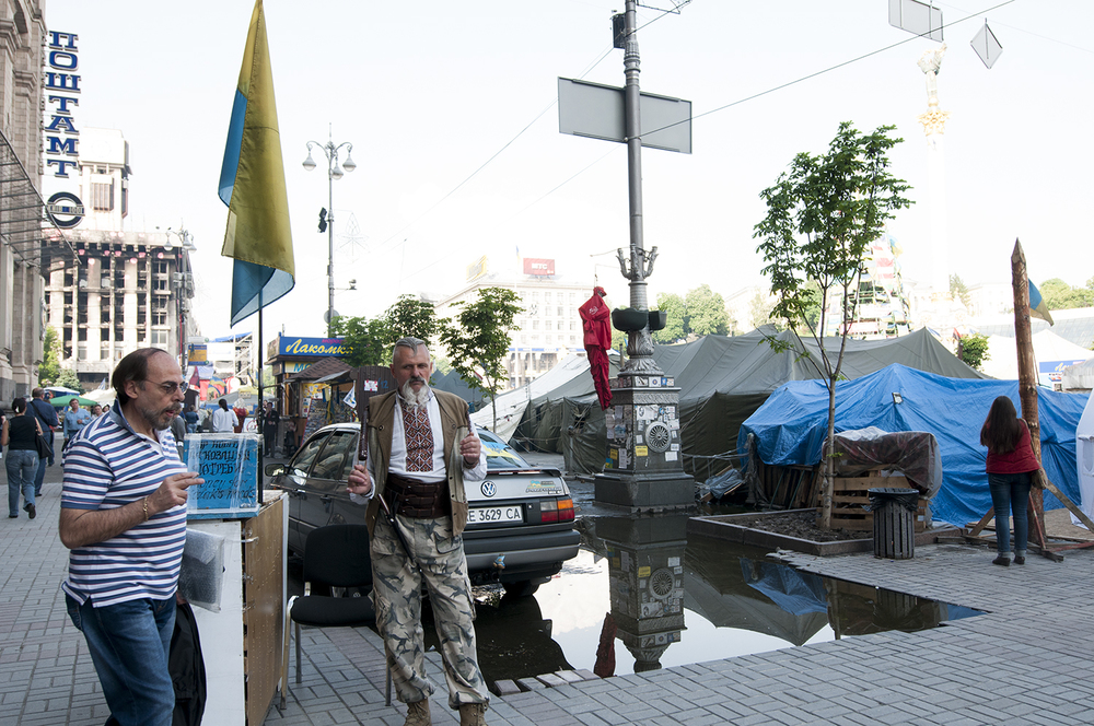 Cossack standing next to on of the numerous donation boxes present on Maidan