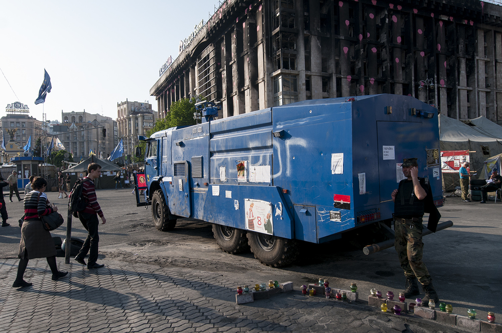 A Maidan activist wearing a bulletproof vet next to an immobilized police vehicle