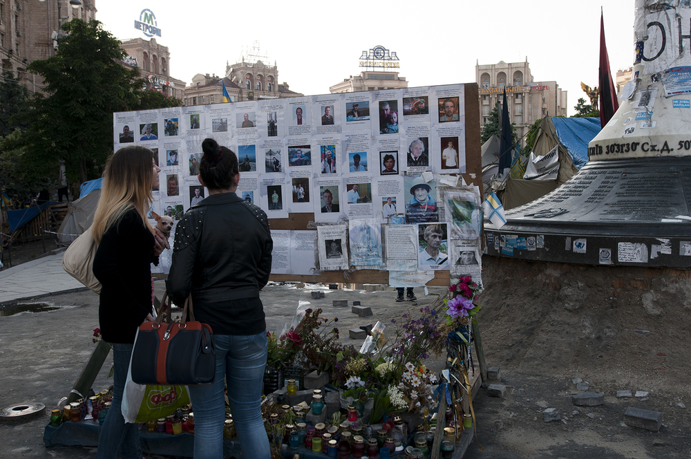 Two young women standing infornt of a board covered with pictures from the Maidan's victimsCar