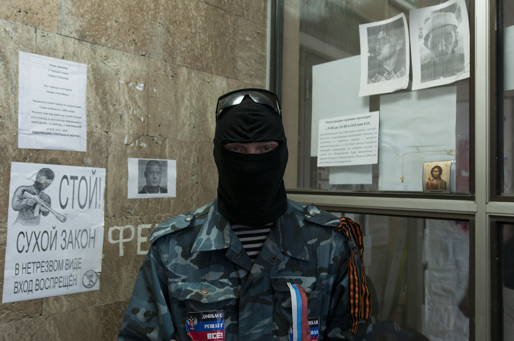 """A pro Russian activist posing in a corner of the regional administration building's main staircase . Pictures of """" provokers"""" are displayed on the windows next to him."""