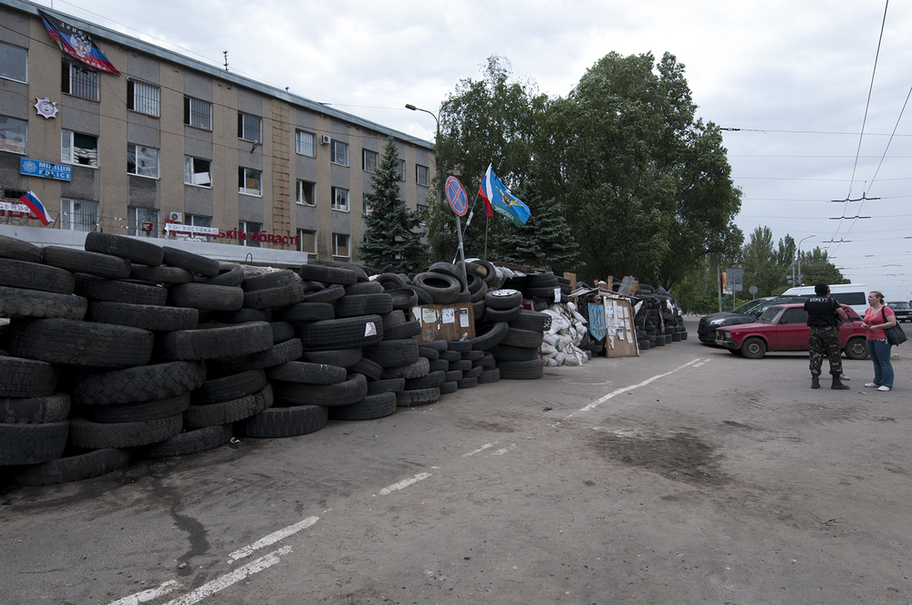 Man wearing a Berkut uniform guarding the barricades in front of Horlivka