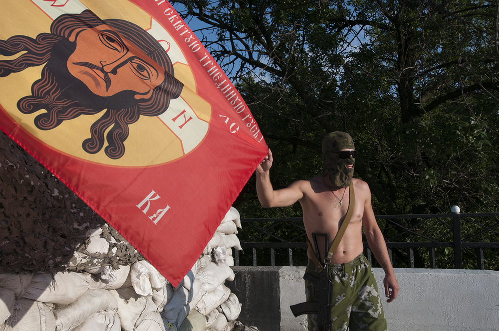 Rameo posing with one of the flags flying over his checkpont. He said that it was really difficult for him as he was used to save lives and he has now taken it away on several during the battles of Sloviansk