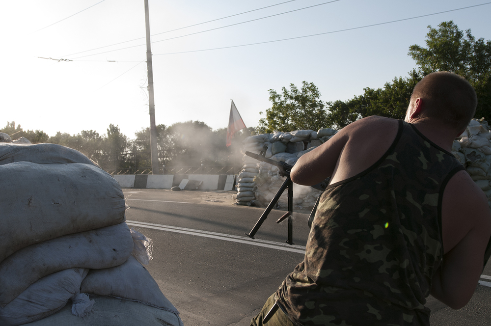DPR solider firing with his light machine gun in direction of the airport.