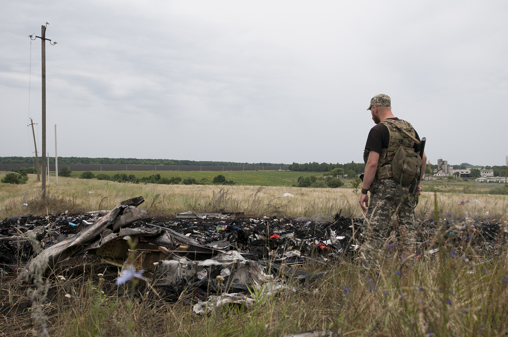 A Separatist solider standing over some of the remains  of the flight MH17