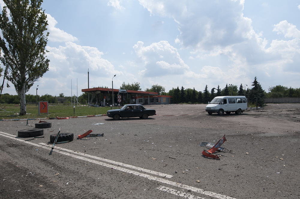 Car dragging a minibus away from a destroyed checkpoint