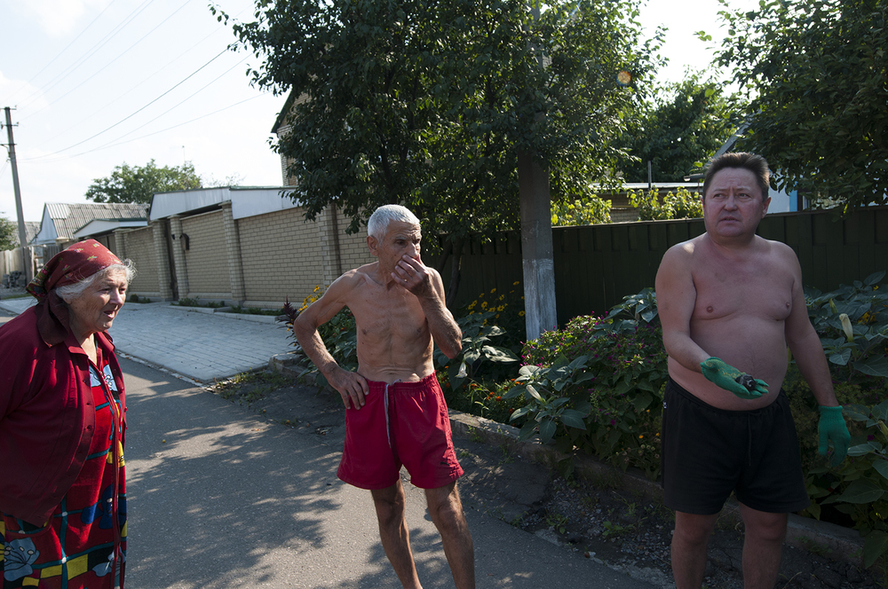 A man displaying a piece of metal that he claim was part of a missile that stroke in his residential area as his neighbour watch