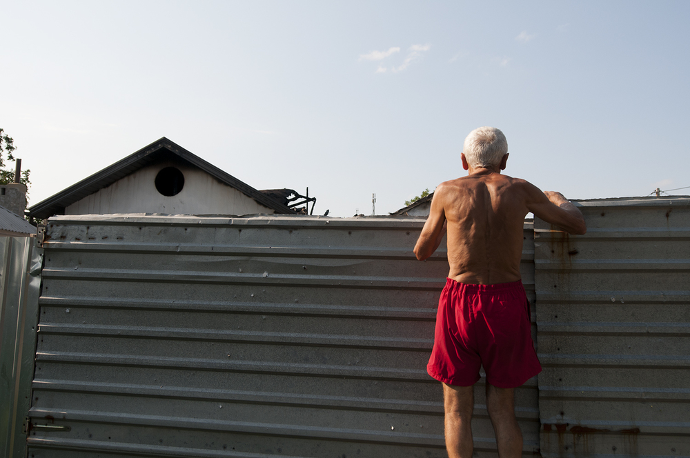 An old men looking over the fence of a house under construction which have caught on fire after being struck by artillery