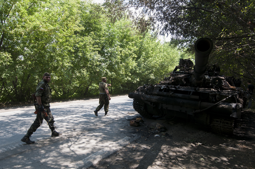 Two separatist soldiers walking past the tank's remains