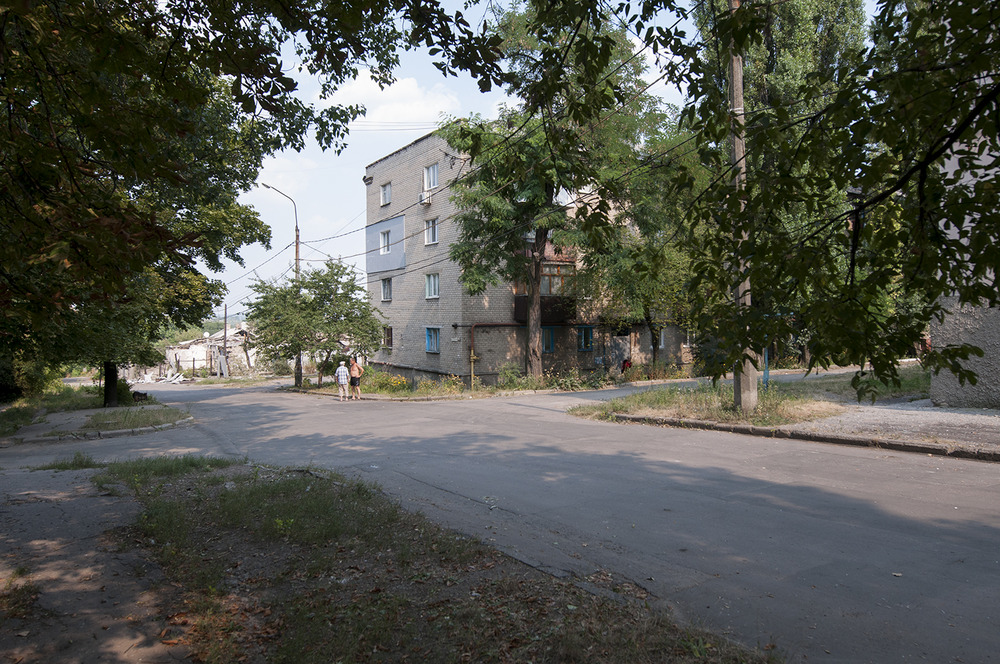 Two men chatting next to buildings which have been hit by shelling