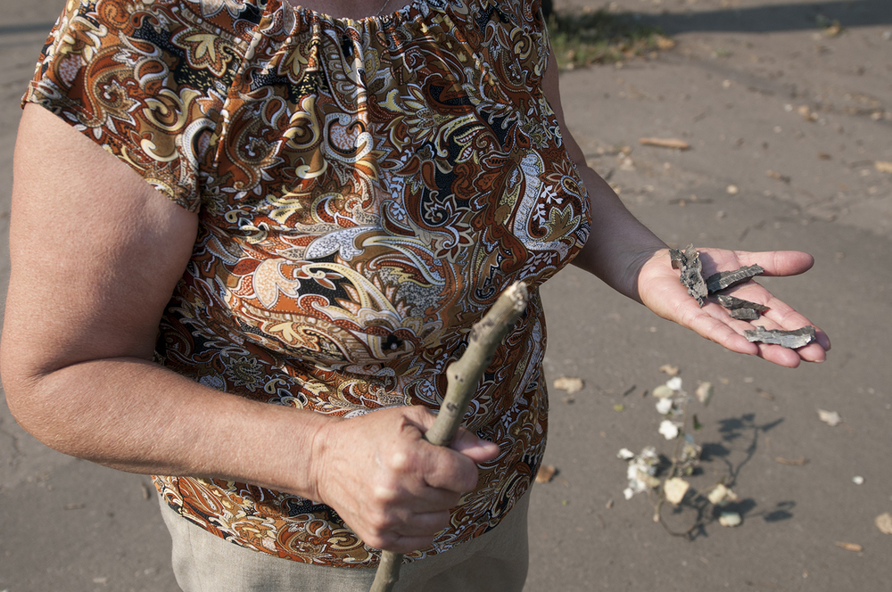 A local woman showing pieces of shrapnel