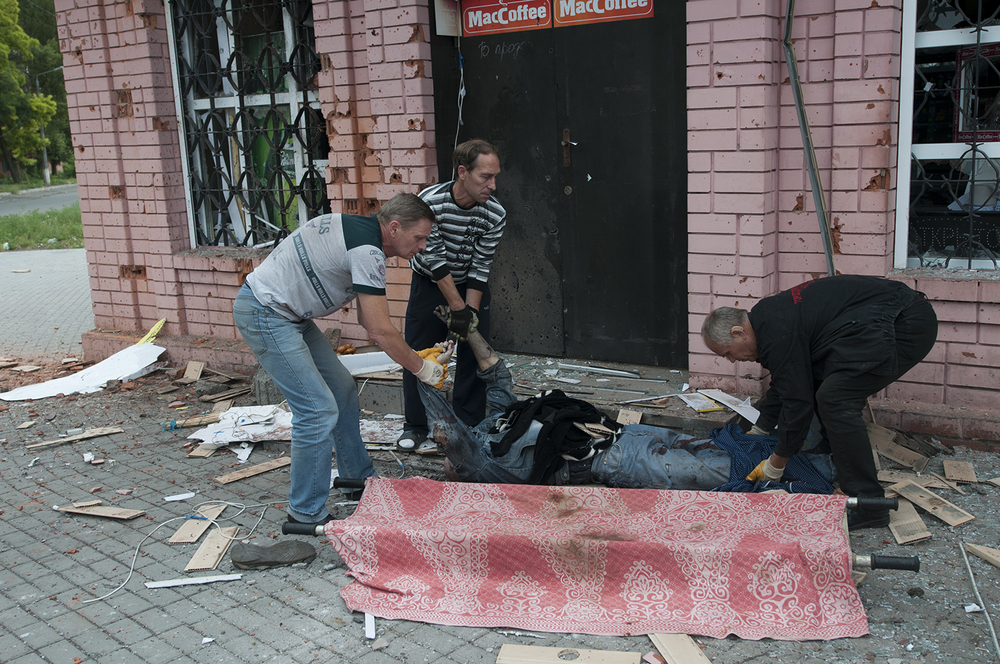 Civilian volunteers taking removing the body