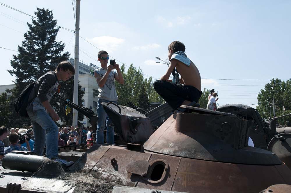 Kids playing around on a burned armored vehicle