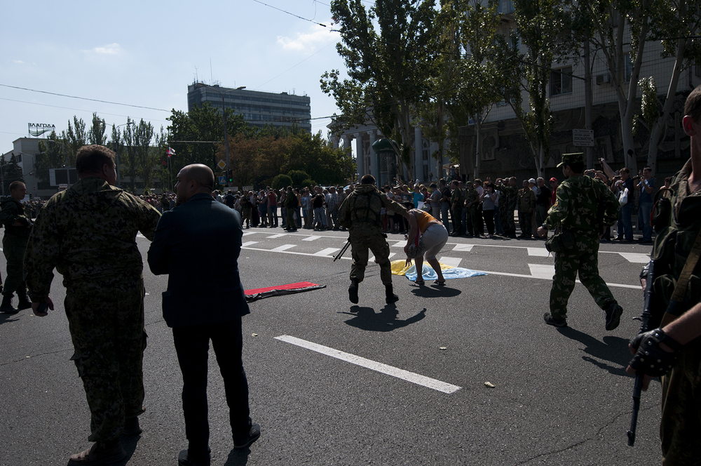 DNR soliders reach for a woman who puts down a Ukrainian flag on the road next to an other one from Pravy Sektor