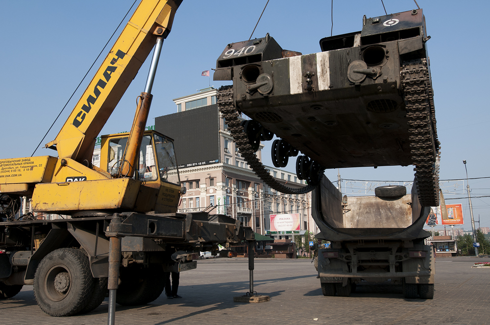 Driver of the crane trying to fit the APC into the back of a truck