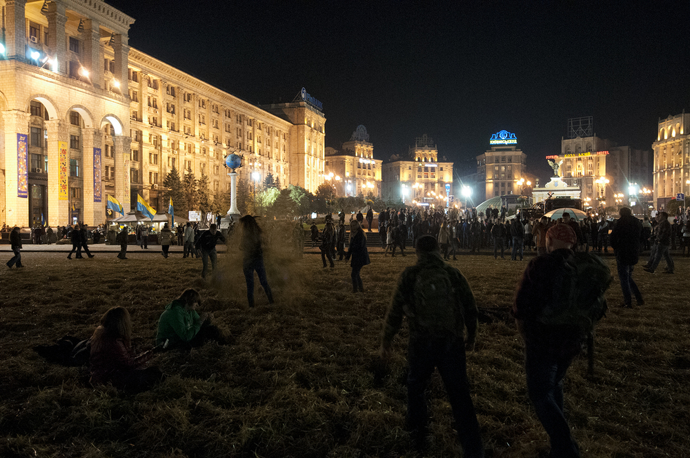 Teens playing in hay as two volunteers walk by on the middle of Maidan Square