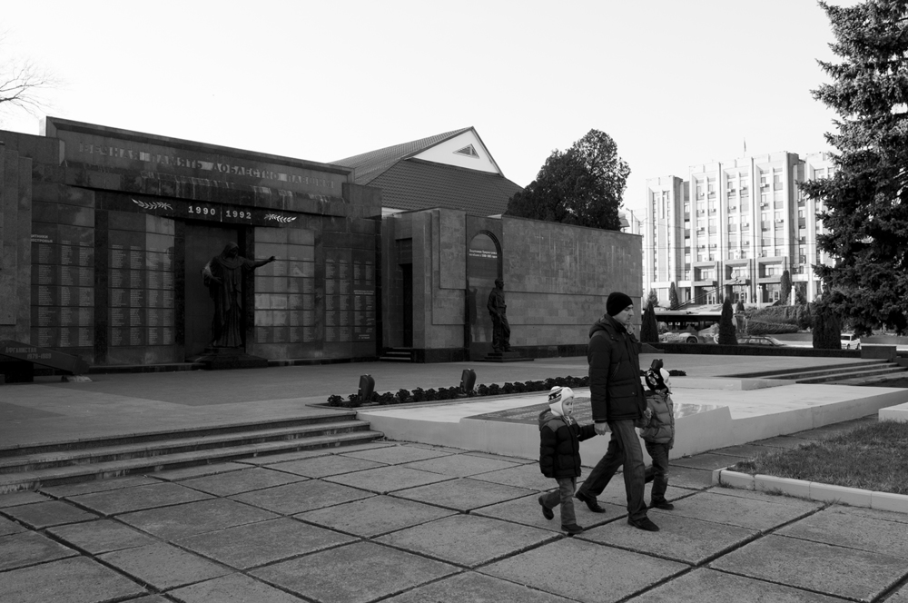 A man walking with his children past the monument commemorating soldiers who died during the war Transnistria fought for its independence.