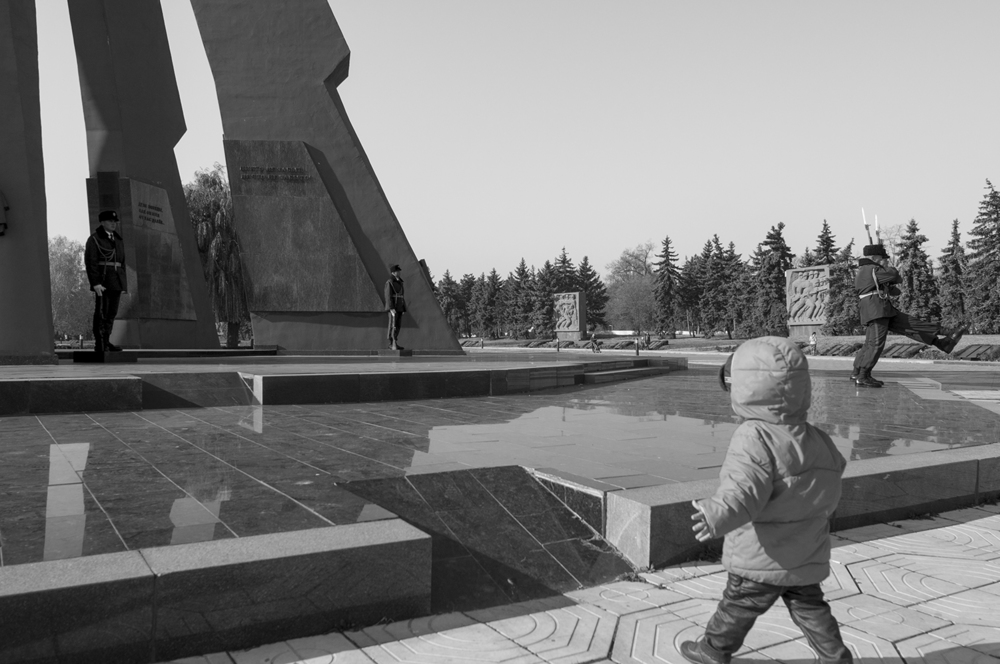 Toddler running in direction of the Monument as she tries to mimic its guards