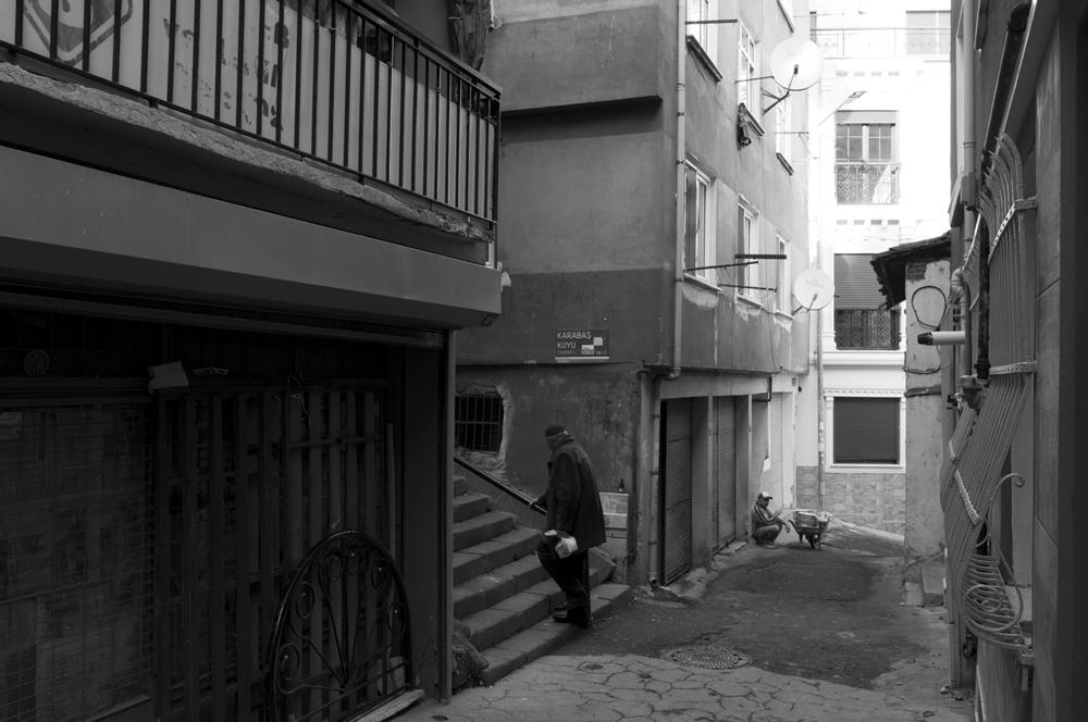 Man walking up to Karabaş Kuyu street as a worker rest next to hiswheelbarrow