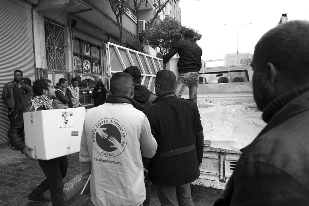 Volunteers and Hayata Destek workers loading relief package in the back of a truck in the center of Suruç. The boxes contain kitchen wear and hygiene products.