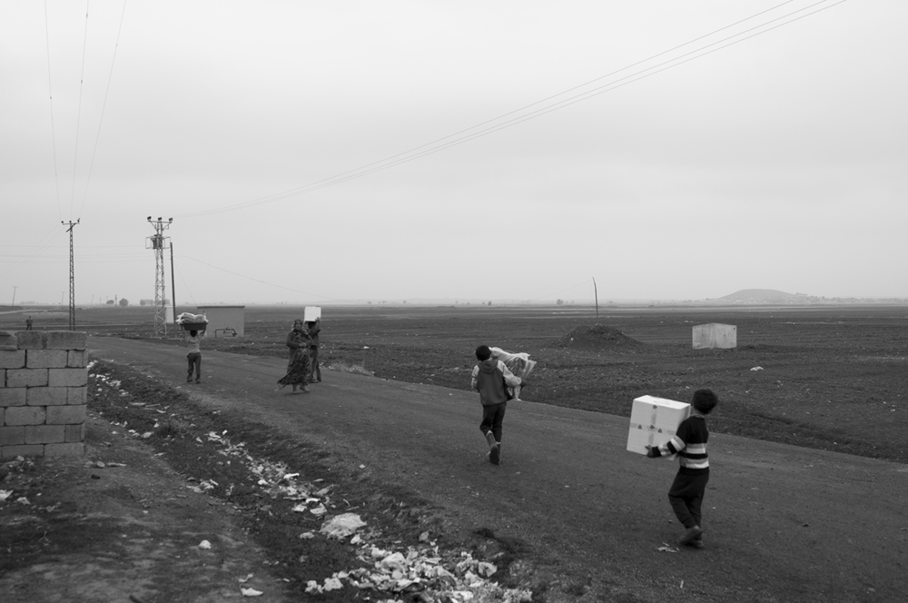Syrian children carrying aid boxes and blanket to their tents;