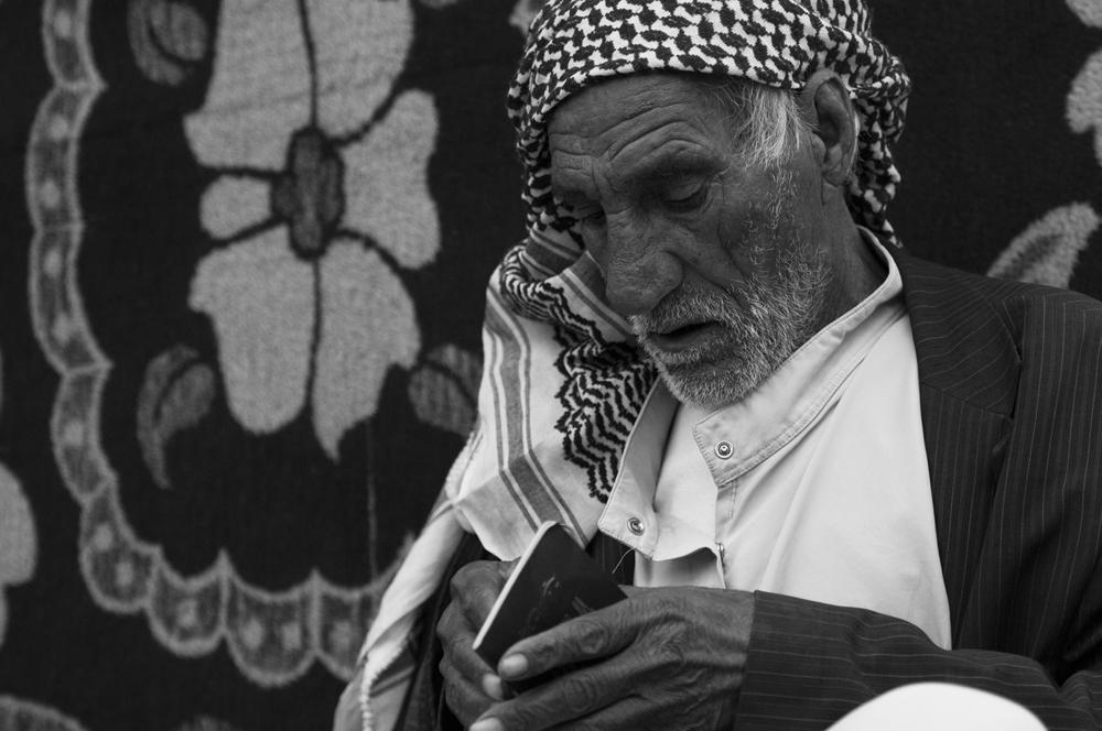 """Baram"" looking at his Syrian passport"