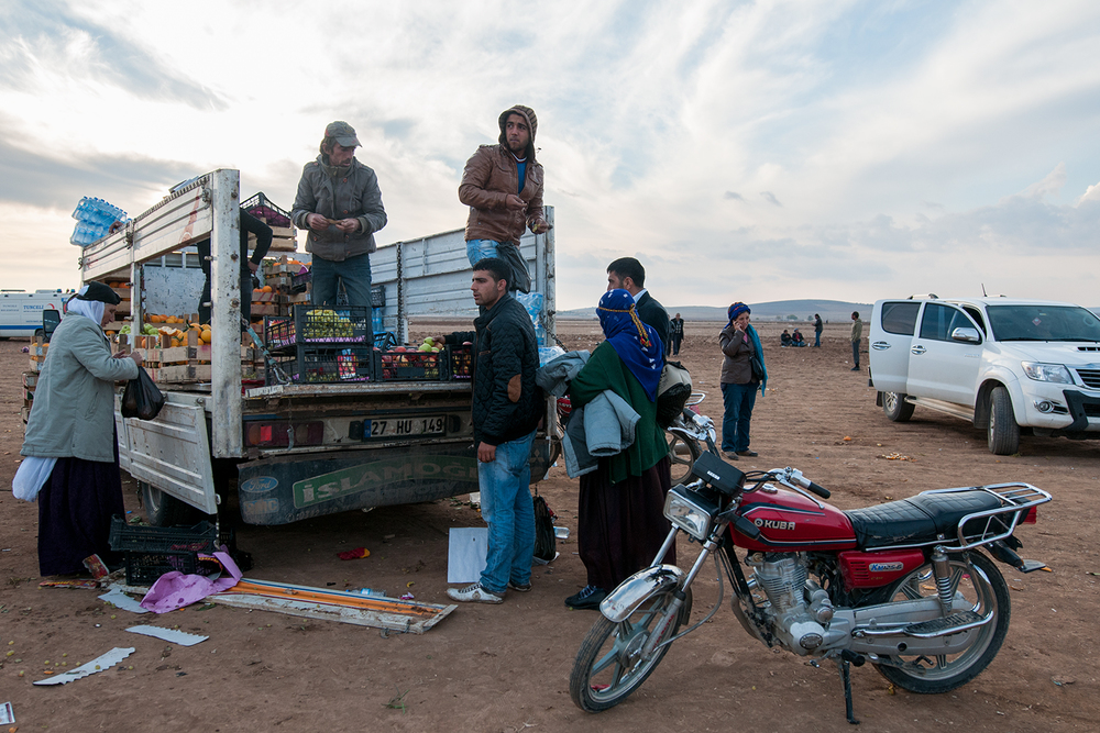 Men selling fruits and vegetables out of a truck in Çaykara
