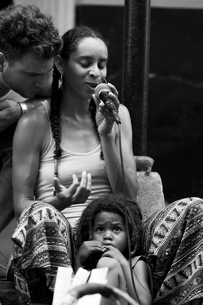 A man whispering in  Kelly Love Jones' ear as she sings with her child sitting between her legs.